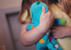 little girl holding a blue stuffed toy